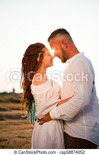 beautiful happy young woman with dreadlocks hugging bearded cute man on sunset - csp58874052