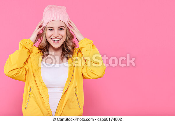 8181b772cc2 Beautiful hipster teenage girl in bright yellow jacket and pink beanie hat  super excited. attractive cool young woman fashion portrait over pastel  pink ...