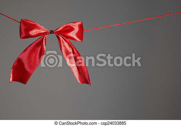 Beautiful holidays red satin bow on gray - csp24033885