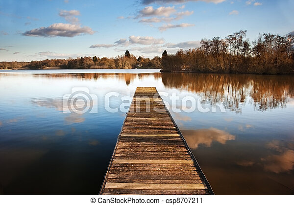 Beautiful image of sunset landscape of wooden fishing jetty on calm lake with clear reflections - csp8707211