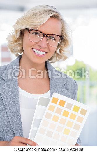 Beautiful interior designer holding up colour samples  - csp13923489