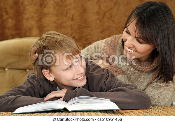 Beautiful joy Caucasian mother with her son reading a book - csp10951456