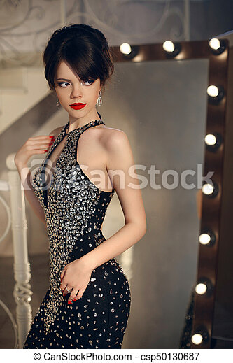 5b6bc9a247694 Beautiful lady in fashion dress posing by mirror with light bulbs. elegant  brunette sexy woman in long gown. attractive girl model with red lips  makeup and ...