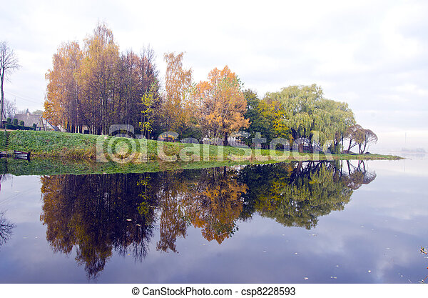 Beautiful lake and autumn trees reflect on water. - csp8228593