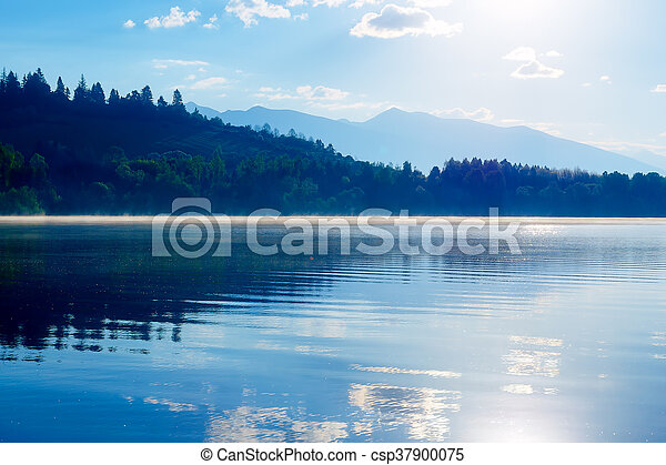 Beautiful lake with mountains in the background at sunrise. - csp37900075