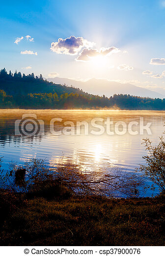 Beautiful lake with mountains in the background at sunrise. - csp37900076