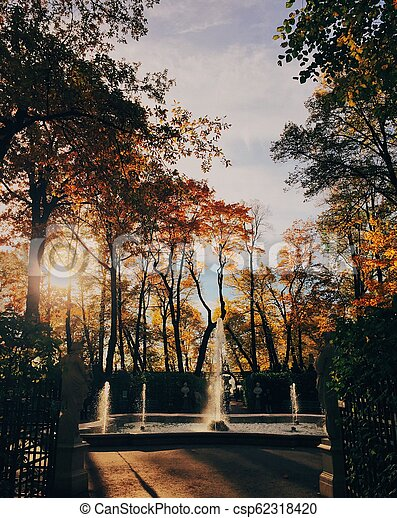 Beautiful landscape in autumn park, fountain, yellow colours, clear sky and sunshine. Nice season. Sunny warm day. Scenery - csp62318420