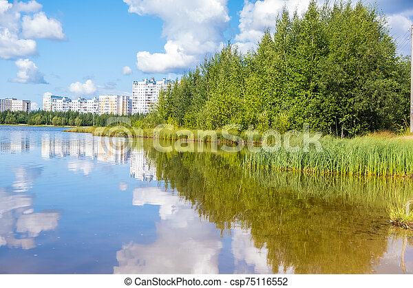 Beautiful landscape of a small lake and city. Light wind on the lake. Clouds are reflected in the water - csp75116552
