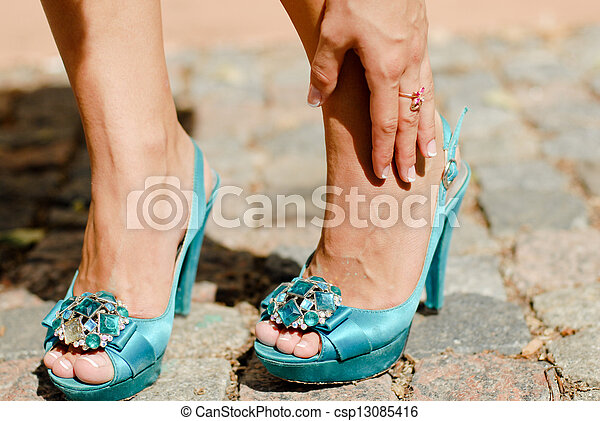 Beautiful legs in blue high heel shoes and hand touching ankle in pain - csp13085416