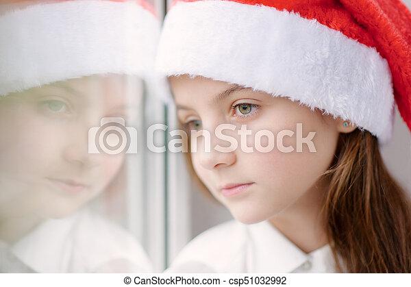 b18e8b1cf73c3 Beautiful little girl in santa hat dreaming by the window. Cute ...