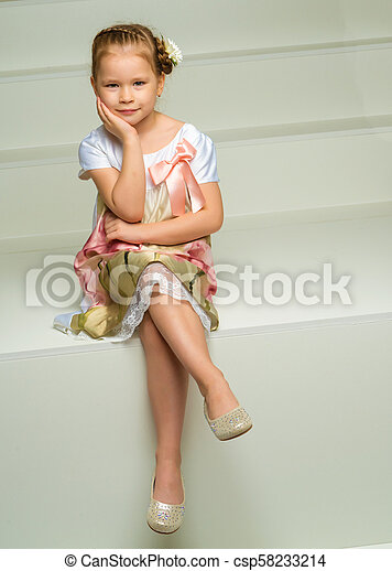 Beautiful little girl is sitting on the white staircase. - csp58233214