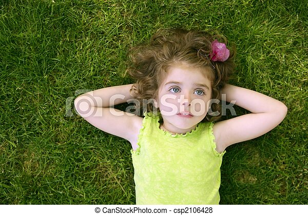 Beautiful little toddler girl happy lying on grass - csp2106428