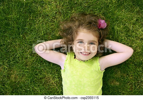 Beautiful little toddler girl happy lying on grass - csp2355115