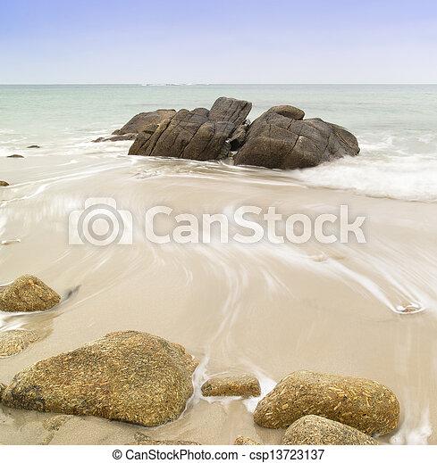 Beautiful long exposure image of golden sand beach at sunset - csp13723137