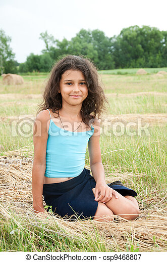 Beautiful long-haired girl in a field - csp9468807