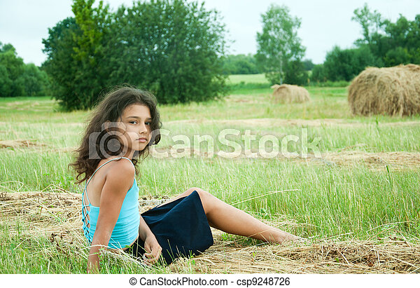 Beautiful long-haired girl in a field - csp9248726