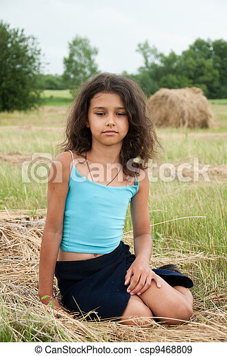 Beautiful long-haired girl in a field - csp9468809