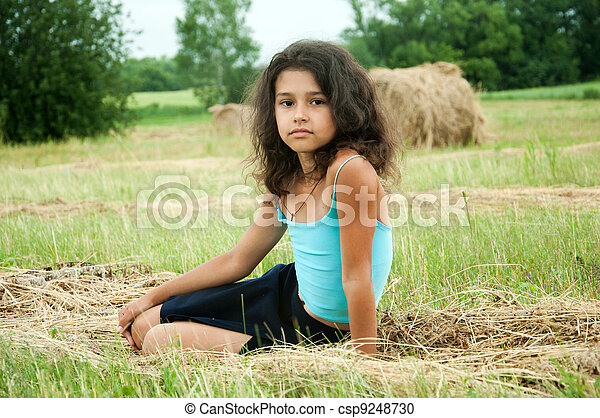 Beautiful long-haired girl in a field - csp9248730