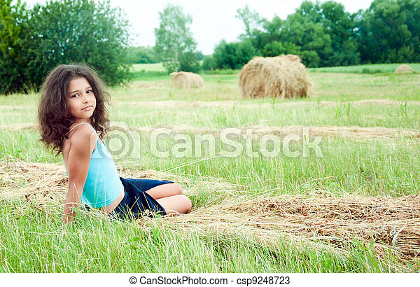 Beautiful long-haired girl in a field - csp9248723