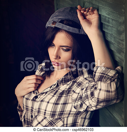 Beautiful makeup teen girl in trendy black and white checkered shirt and blue summer cap thinking on blue wooden doors background looking down. Short hairstyle. - csp46962103