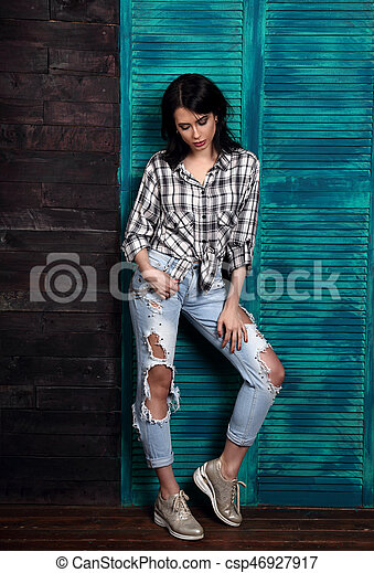 Beautiful makeup woman in trendy black and white checkered shirt, blue ripped jeans, fashion shoes thinking and looking down on blue wooden background. - csp46927917
