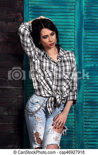 Beautiful makeup woman in trendy black and white checkered shirt and blue ripped jeans thinking and looking down on blue wooden background. Short hairstyle. contrast closeup portrait. - csp46927918