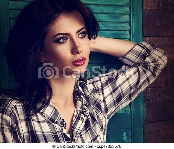 Beautiful makeup woman in trendy black and white checkered shirt looking relax and  thinking on blue wooden doors background. Short hairstyle. Closeup contrast toned portrait - csp47023570