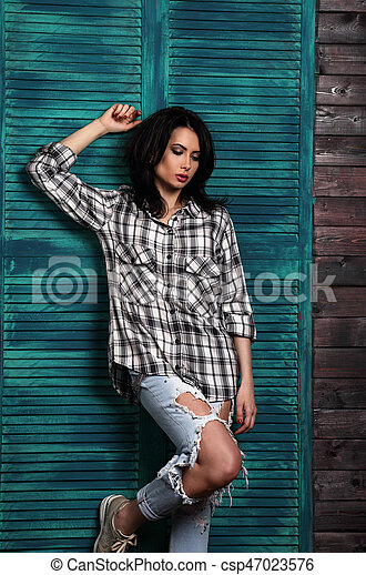 Beautiful makeup woman in trendy black and white checkered shirt, blue ripped jeans thinking and looking down on blue wooden doors background. - csp47023576