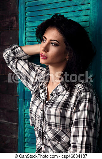 Beautiful makeup woman in trendy black and white checkered shirt thinking on blue wooden background. Short hairstyle - csp46834187