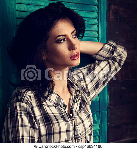 Beautiful makeup woman in trendy black and white checkered shirt thinking on blue wooden background. Short hairstyle. Toned contrast closeup portrait - csp46834188