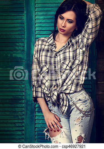 Beautiful makeup woman in trendy black and white checkered shirt and blue ripped jeans - csp46927921