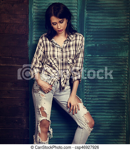 Beautiful makeup woman in trendy black and white checkered shirt, blue ripped jeans thinking and looking down on blue wooden background. Toned portrait - csp46927926