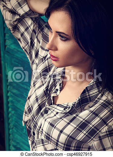 Beautiful makeup woman profile in trendy black and white checkered shirt thinking on blue wooden background. Short hairstyle. contrast closeup portrait. Toned - csp46927915