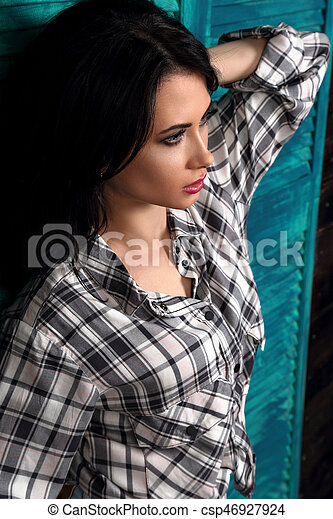 Beautiful makeup woman profile in trendy black and white checkered shirt thinking on blue wooden background. Short hairstyle. contrast closeup portrait - csp46927924