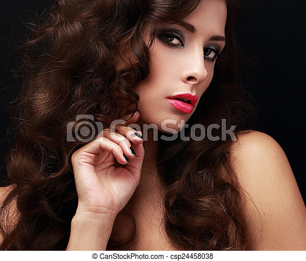 Beautiful makeup woman with long brown curly hair on black - csp24458038