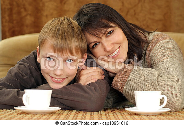 Beautiful mama and son sitting on the couch with a cup - csp10951616