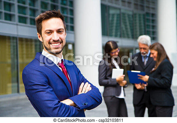 Beautiful man on the background of business people  - csp32103811