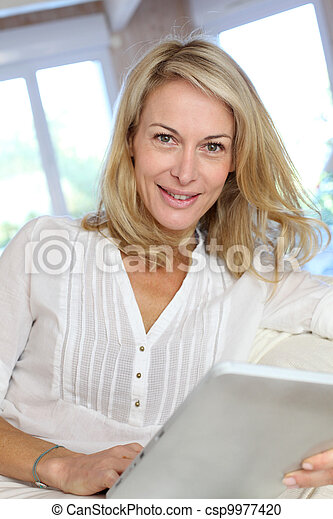Beautiful mature woman using electronic tablet at home - csp9977420