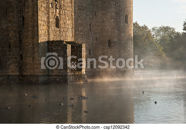 Beautiful medieval castle and moat at sunrise with mist over moat and sunlight behind castle - csp12092342