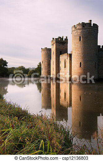Beautiful medieval castle and moat at sunrise with mist over moat and sunlight behind castle - csp12136803