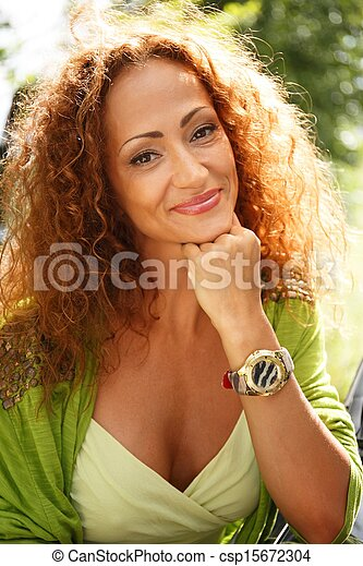Beautiful middle-aged redhead smiling woman outdoors - csp15672304