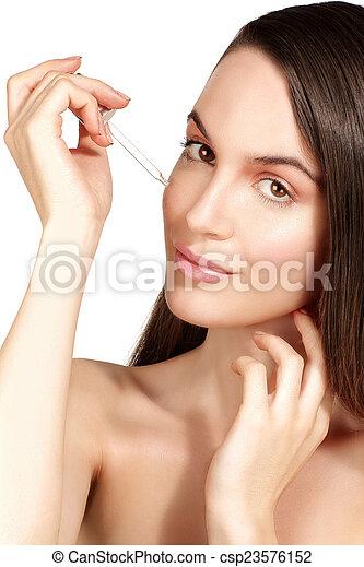 Beautiful model applying a cosmetic skin serum treatment - csp23576152