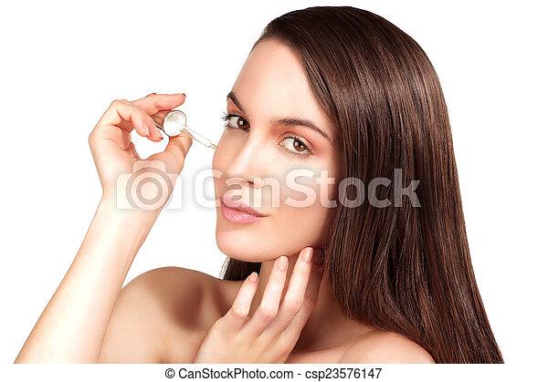 Beautiful model applying a cosmetic skin serum treatment - csp23576147