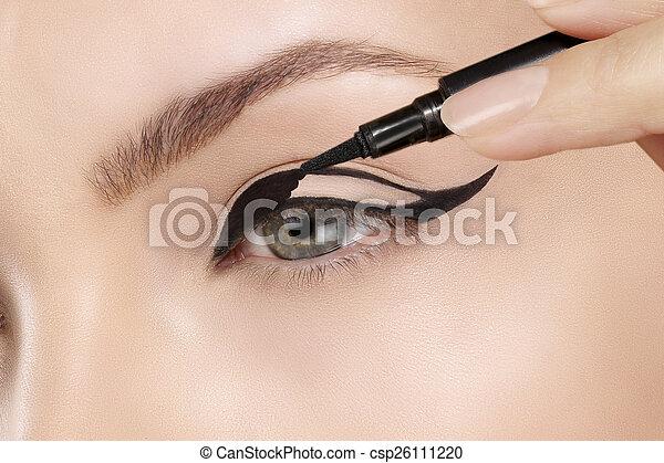 Beautiful model applying eyeliner closeup on eye - csp26111220
