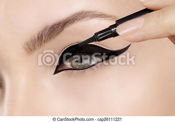 Beautiful model applying eyeliner closeup on eye - csp26111221