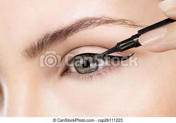 Beautiful model applying eyeliner closeup on eye - csp26111223