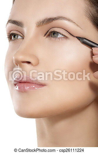 Beautiful model applying eyeliner closeup on eye - csp26111224