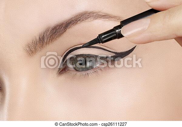 Beautiful model applying eyeliner closeup on eye - csp26111227