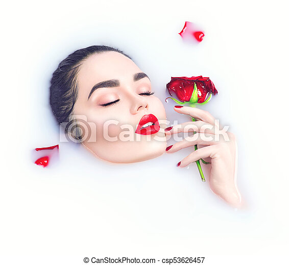 Beautiful model woman with bright makeup holding red rose flower in her hand and relaxing in milk bath - csp53626457