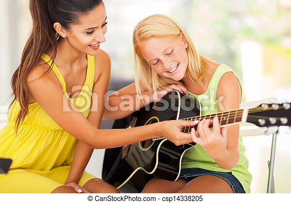 beautiful music teacher tutoring young girl to play guitar - csp14338205